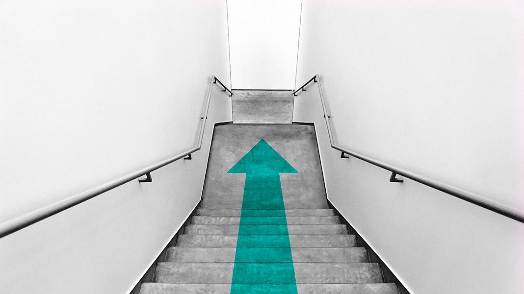 escaleras con una flecha azul pintada sobre el suelo