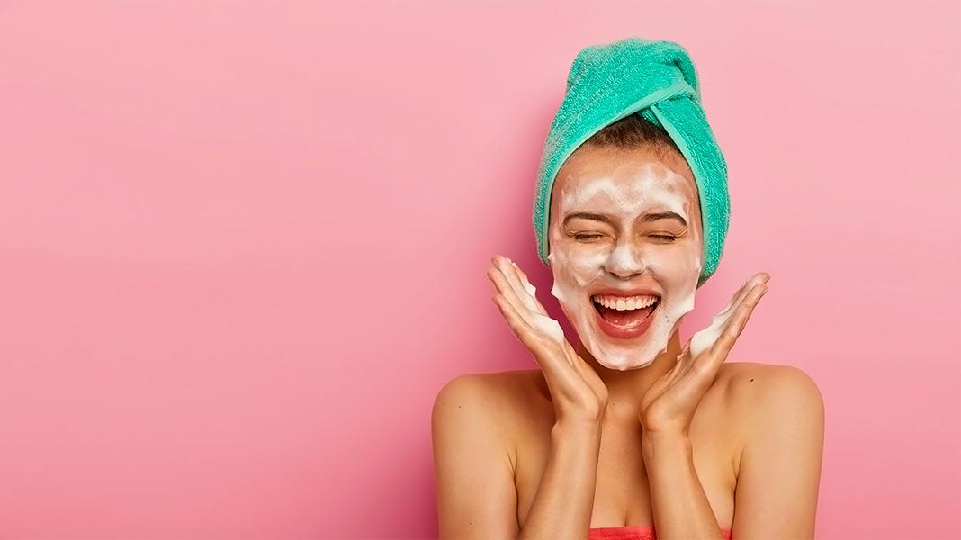 chica sonriendo con una mascarilla de belleza en la cara y una toalla en el pelo